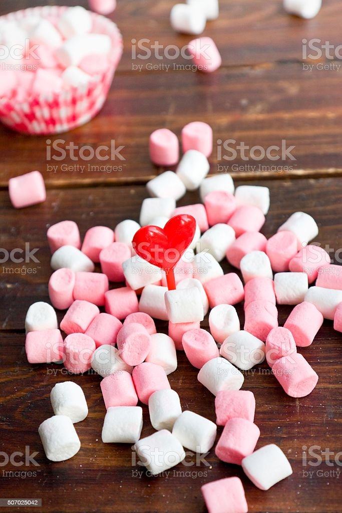 Marshmallows with hearts on wooden background stock photo