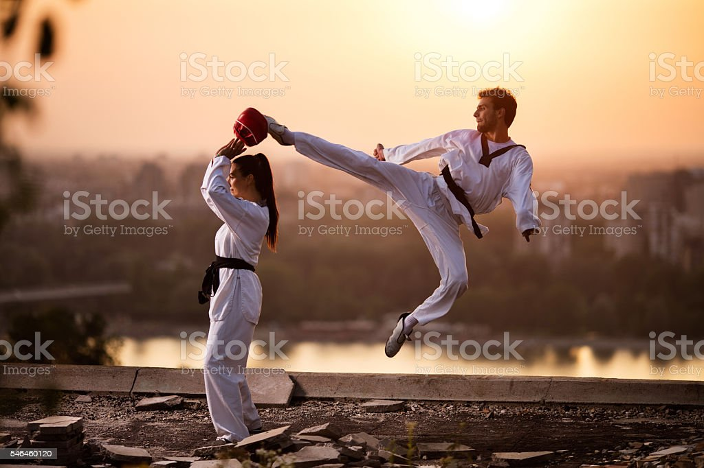 Martial artist fighter exercising with female partner at sunset. stock photo