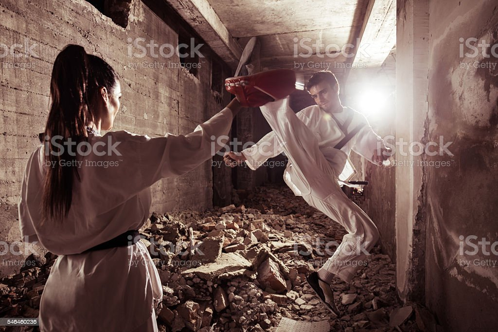 Martial artist practicing high kick with his female partner. stock photo