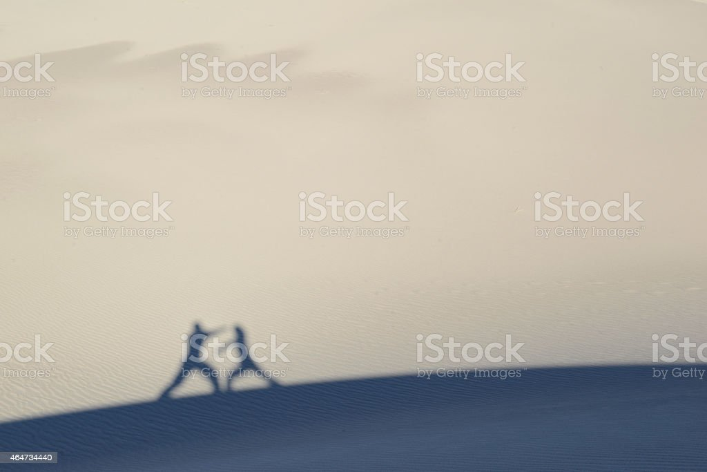 Martial artists silhouettes and shadows against sand dunes stock photo