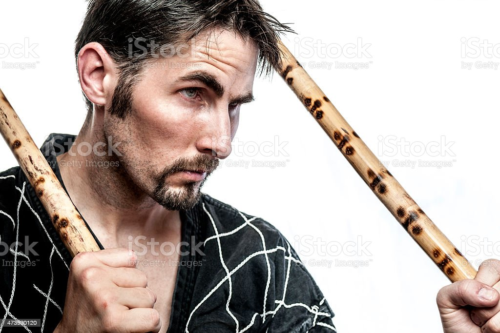 Martial arts master with bamboo sticks stock photo
