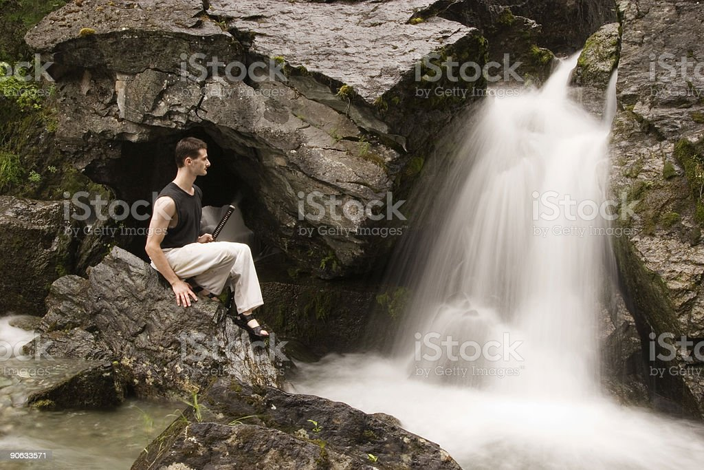 martial arts - meditation next to waterfall stock photo