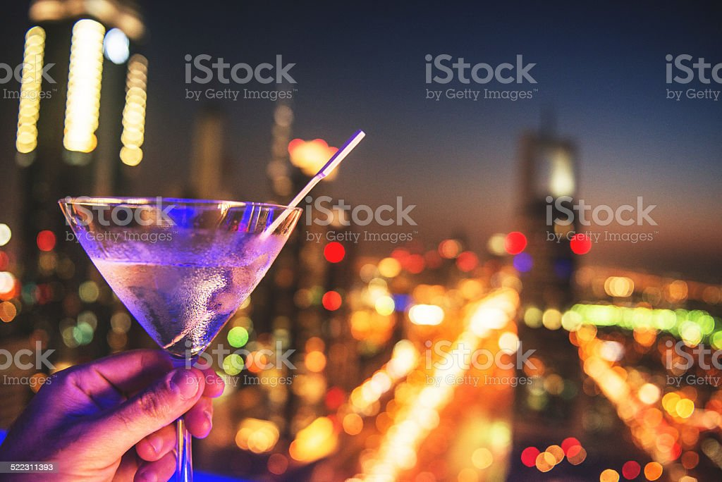 martini drink with city lights of Dubai downtown stock photo