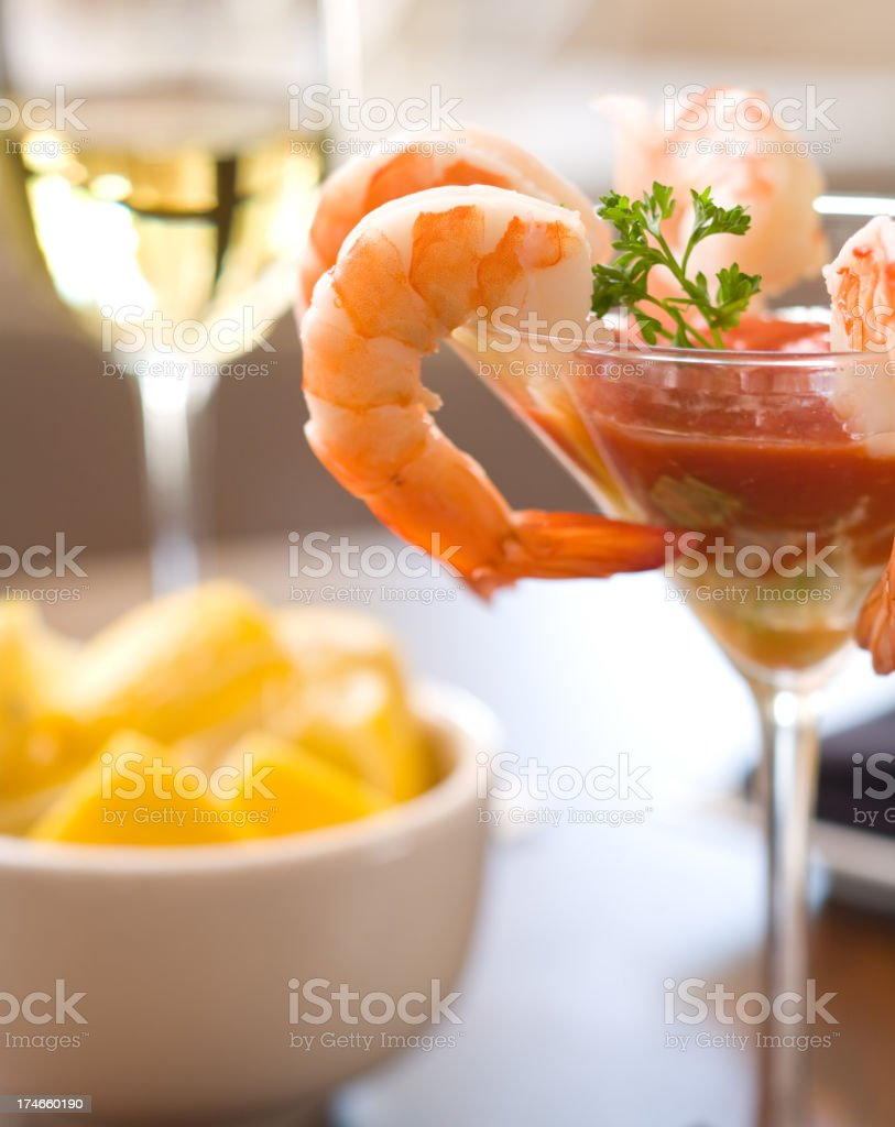 A martini glass of shrimp cocktail and a bowl of lemons royalty-free stock photo