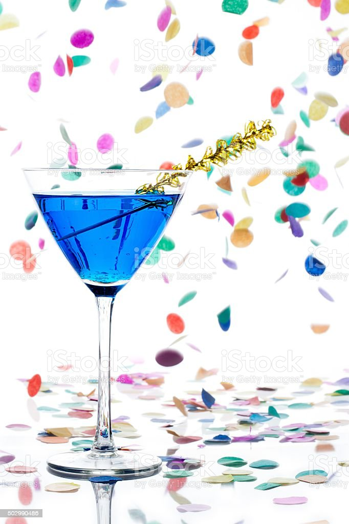 martini glass with blue alcohol and yellow streamer stock photo