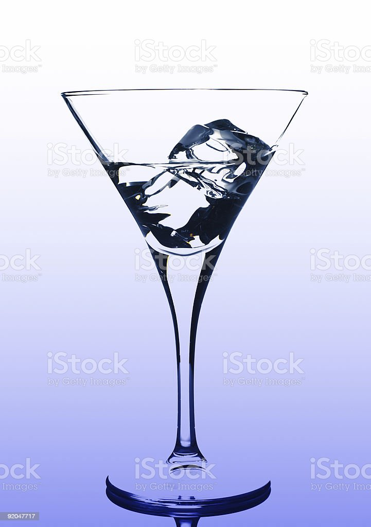 martini glass with ice cubes and some drink on blue stock photo