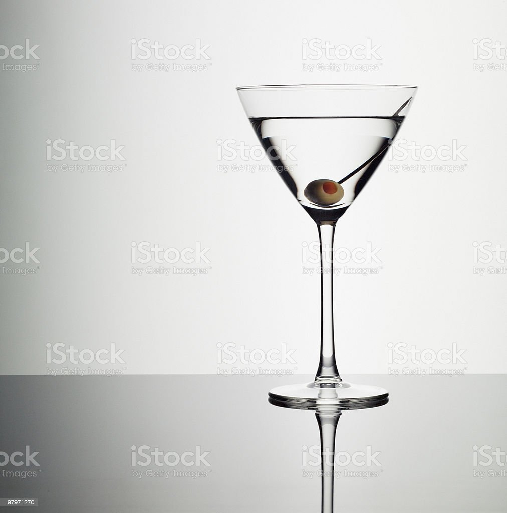 Martini in glass with green olive stock photo