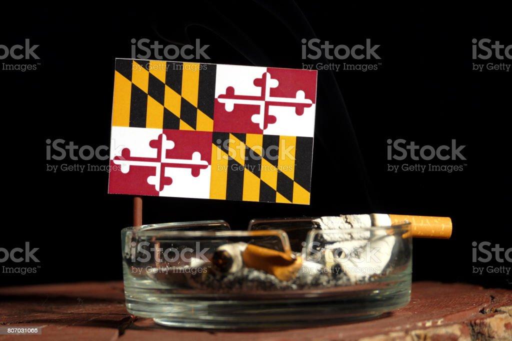 Maryland flag with burning cigarette in ashtray isolated on black background stock photo