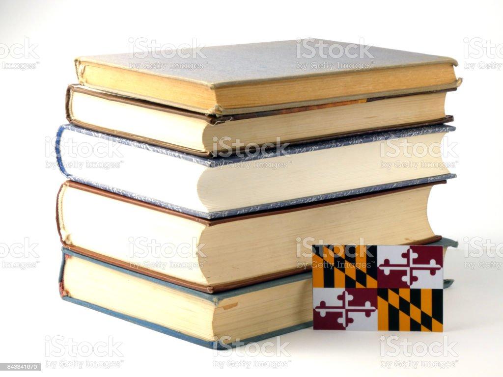 Maryland flag with pile of books isolated on white background stock photo