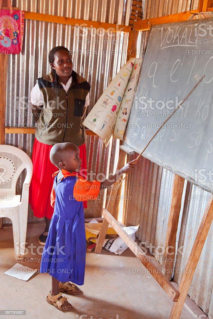 Masai child at blackboard watched by teacher. stock photo