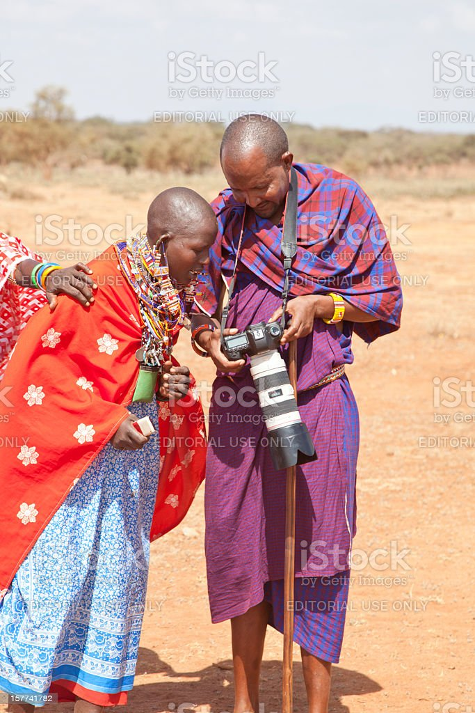 Masai headman showing images on camera screen to young woman. stock photo