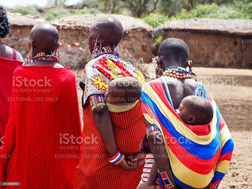 Masai women carrying their kids on their back near Amboseli, Kenya stock photo