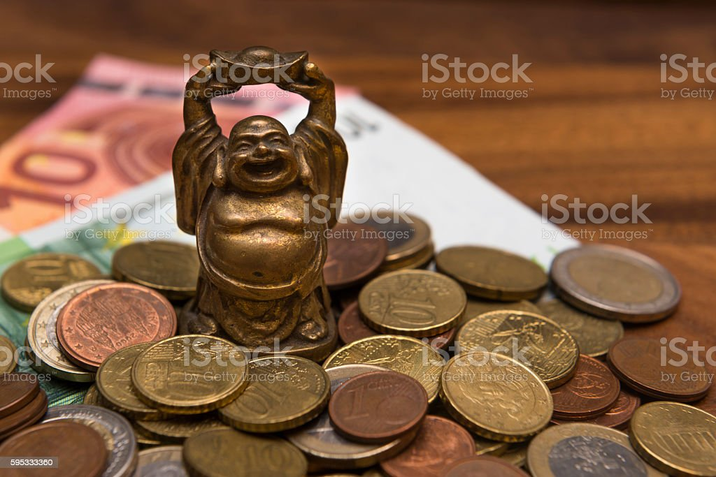 Mascot netske Hotei coins Euro banknotes on a wooden table stock photo