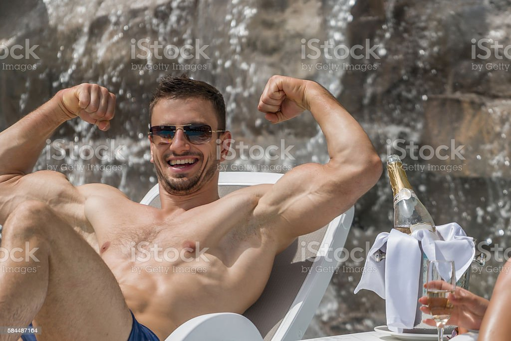 Mascular man lying sunbed stock photo