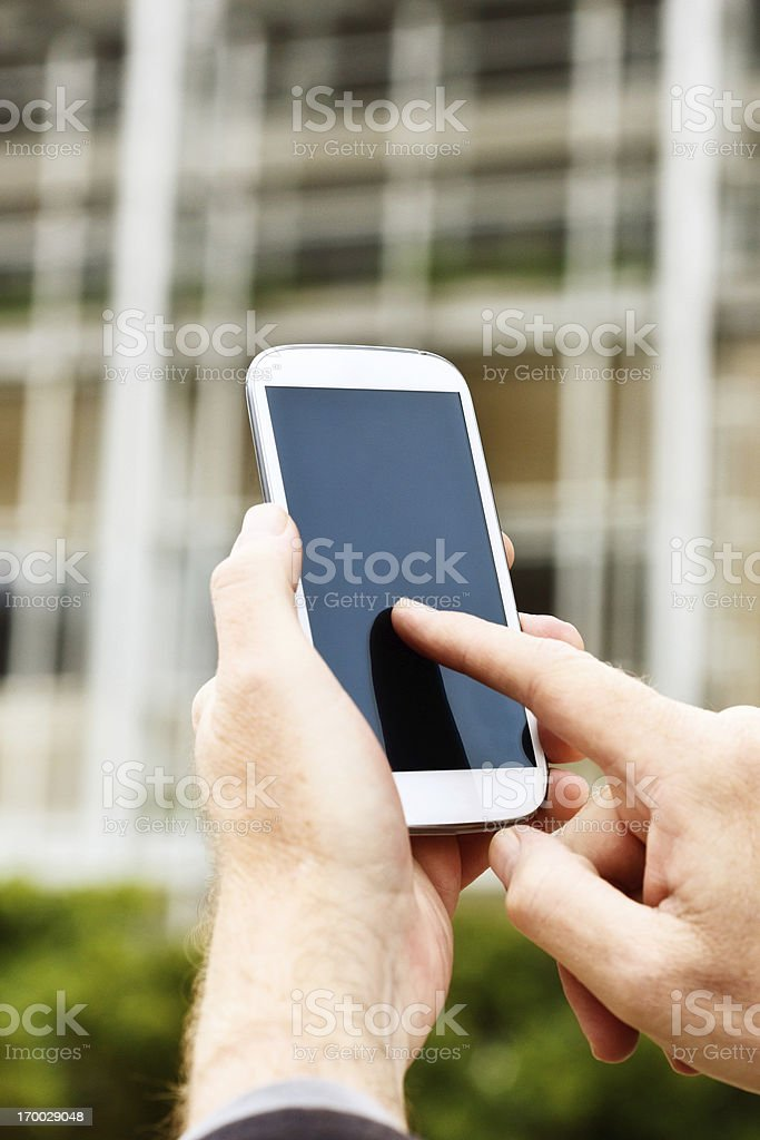 Masculine hand tapping touch screen of smart phone outside building royalty-free stock photo