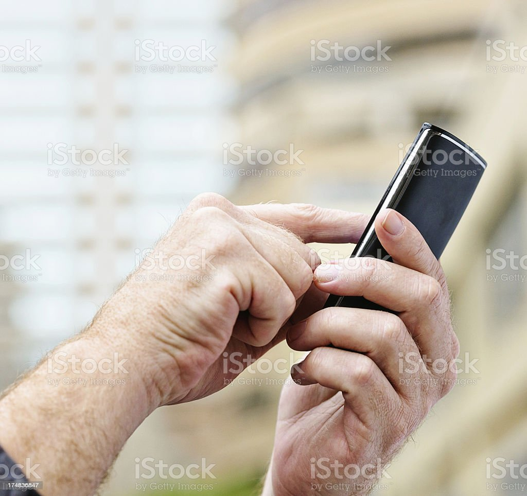 Masculine hands using smart phone in city exterior royalty-free stock photo