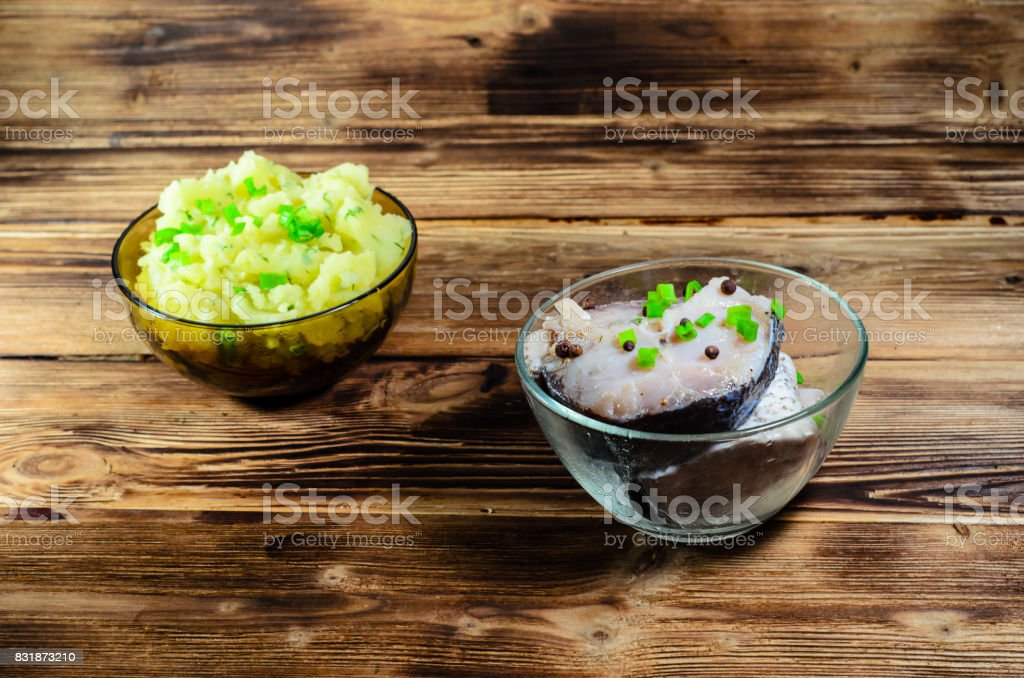 Mashed potatoes and marinated carp on wooden table stock photo