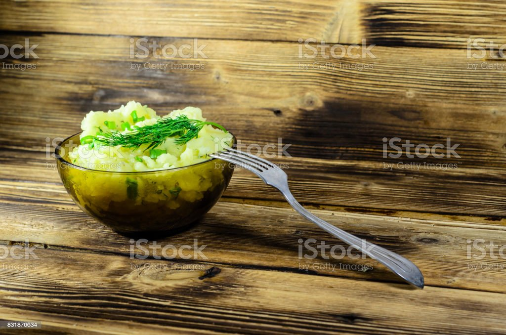 Mashed potatoes in glass bowl on wooden table stock photo