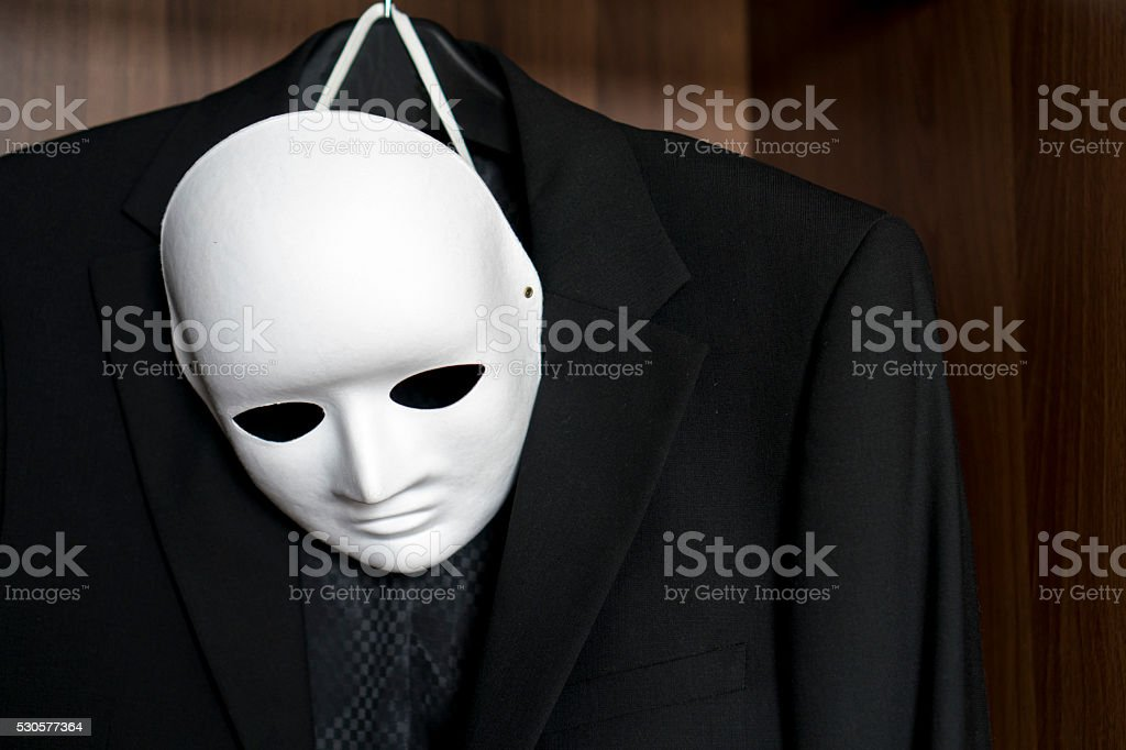 mask and office suit hanging in closet stock photo