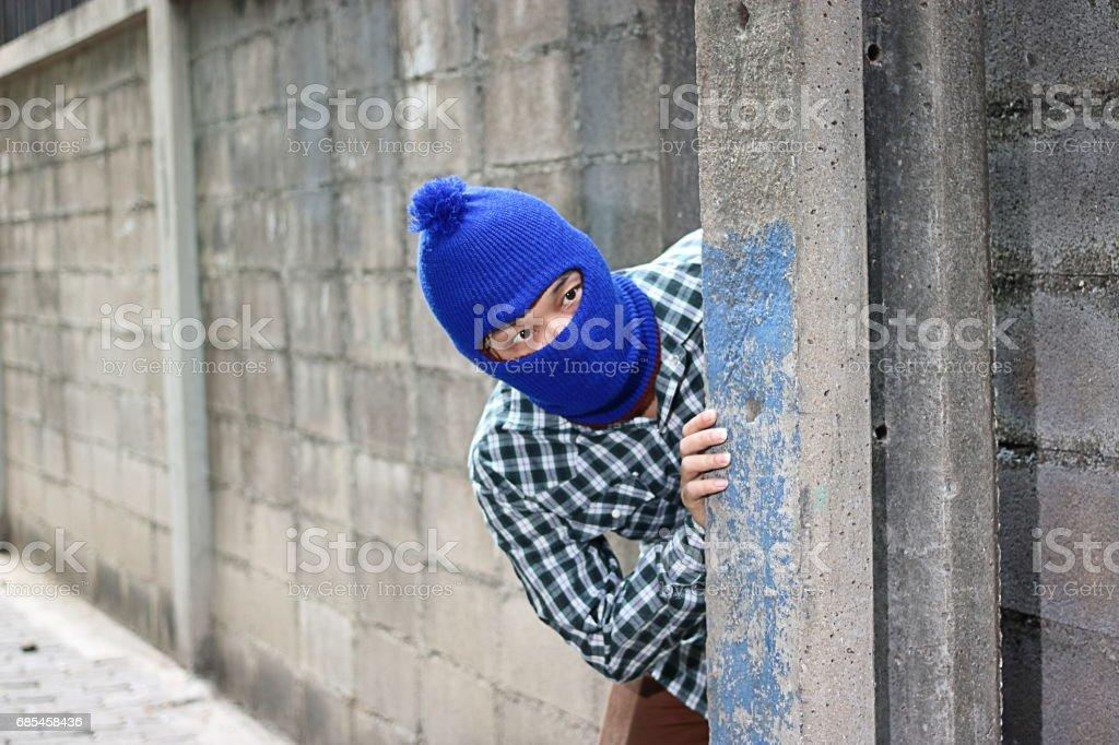 Masked burglar sneaking behind concrete pole before the burglary. Crime concept stock photo