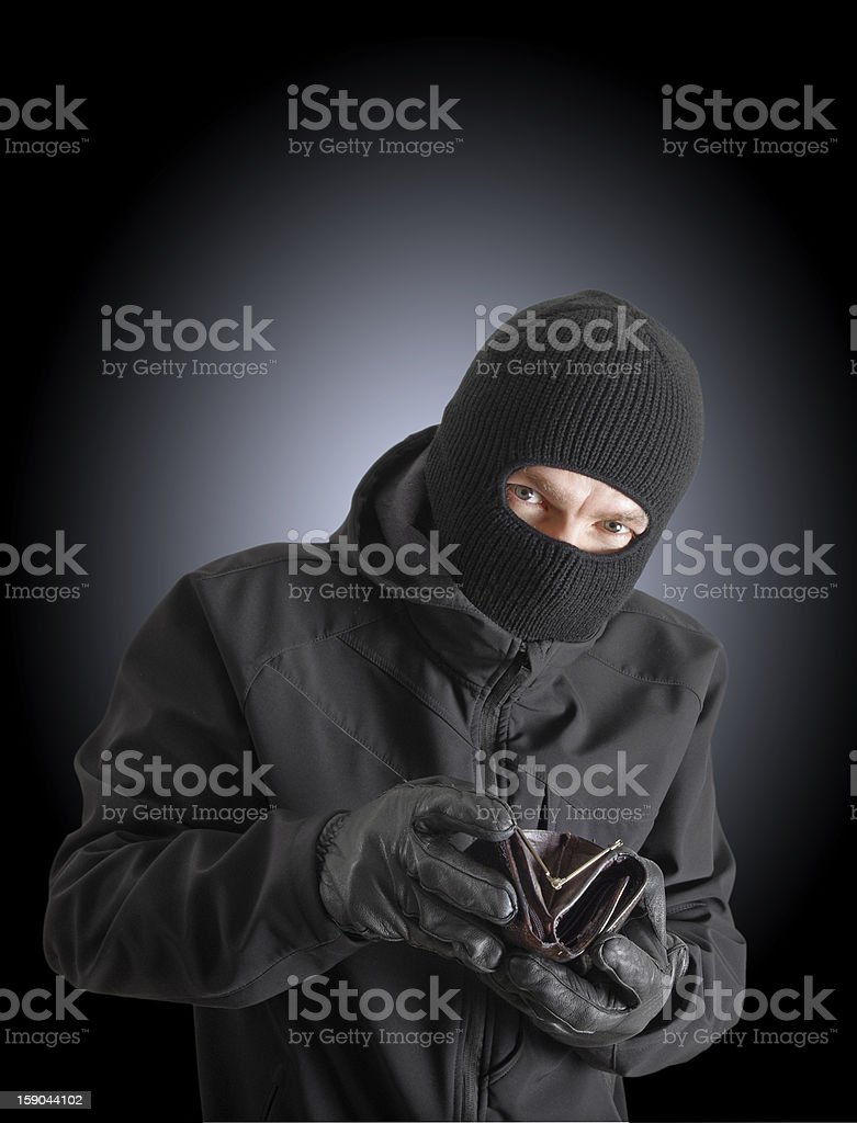 Masked criminal holding a stolen leather purse royalty-free stock photo