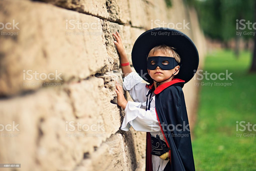 Masked little boy hero perparing to climb the wall stock photo