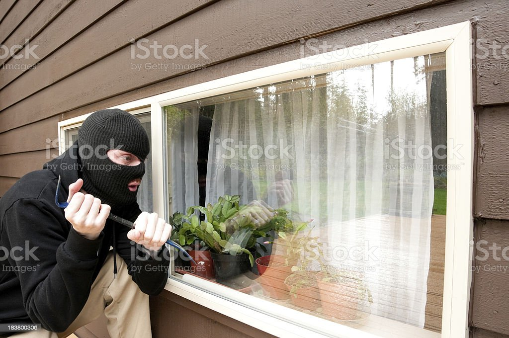 Masked man breaking into a house royalty-free stock photo