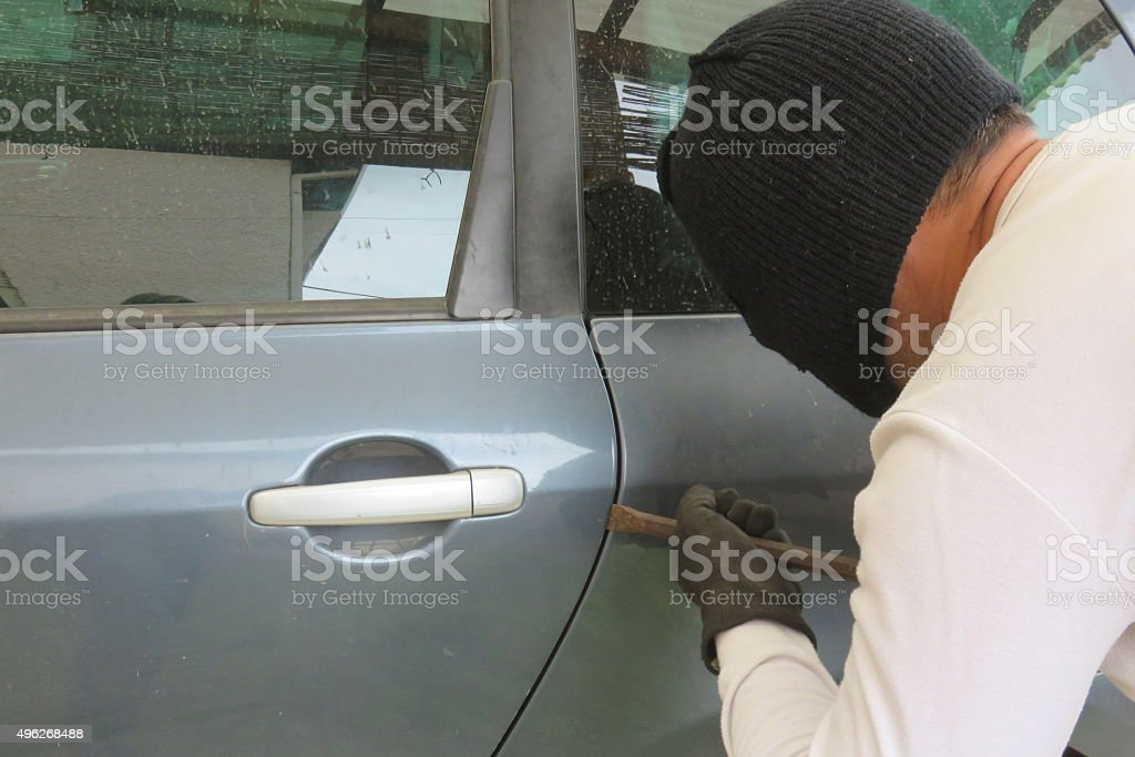 Masked Man Breaking Into Car With Crowbar stock photo