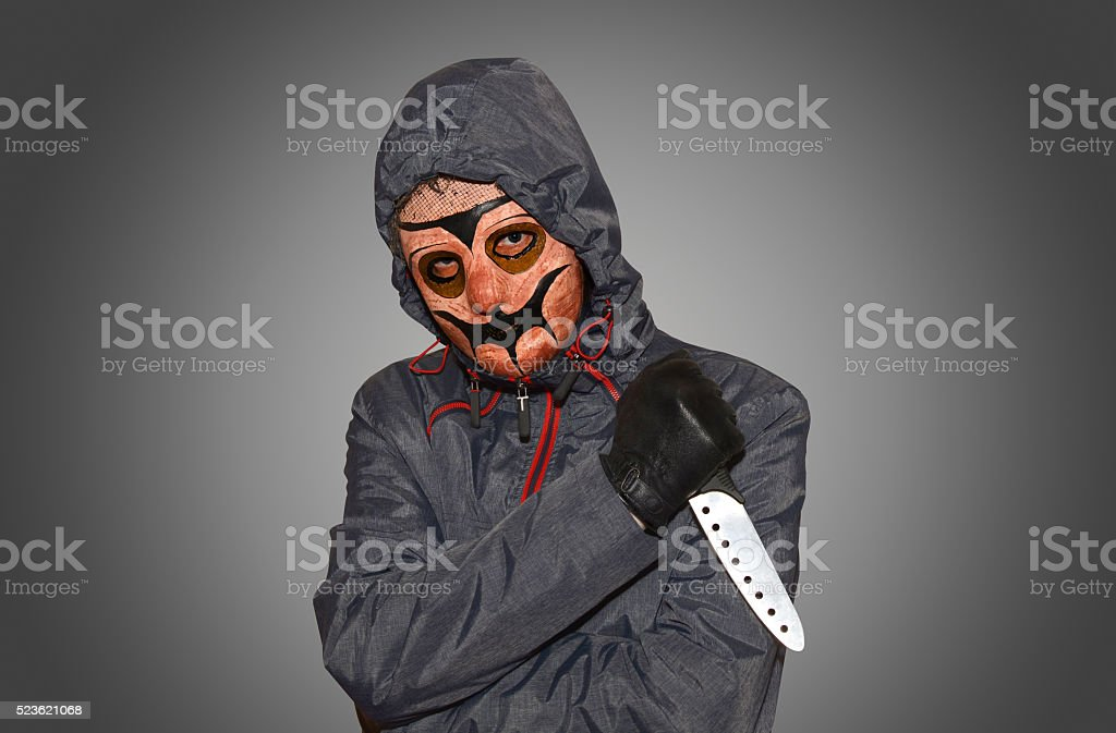 masked man with a knife stock photo