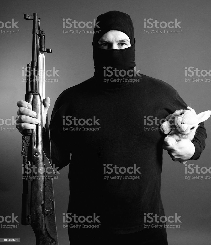 Masked man with gun and bunny stock photo