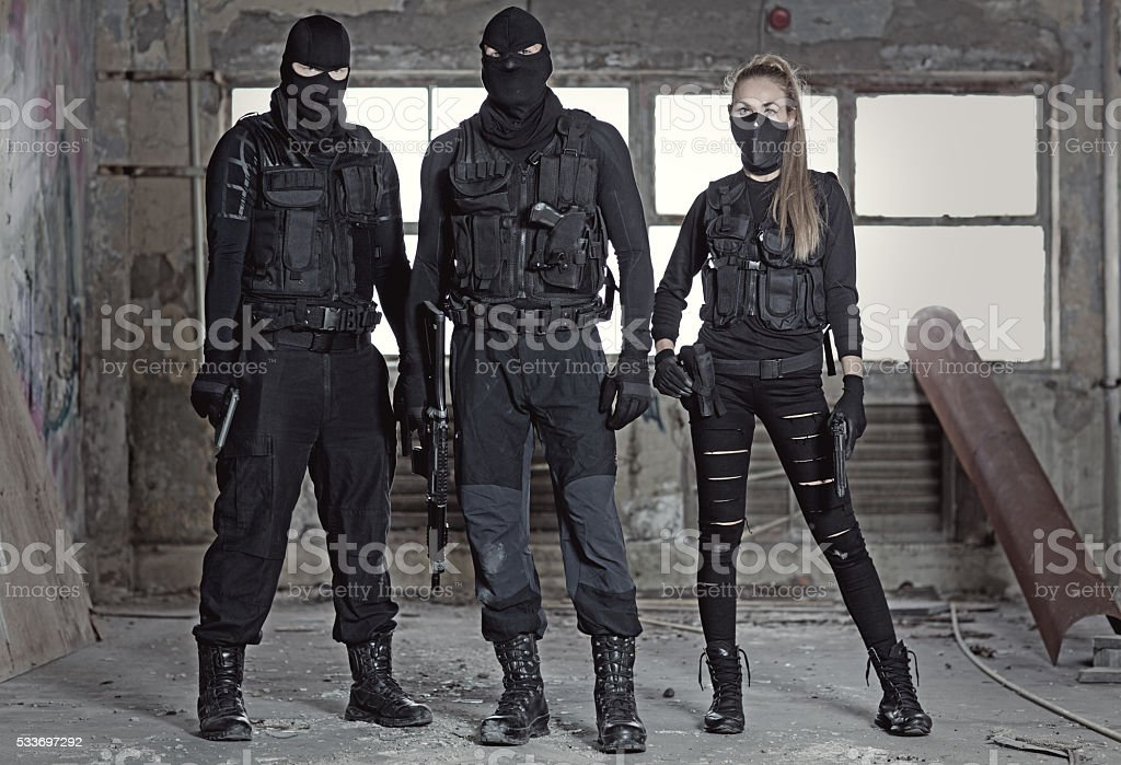 Masked military swat team members holding weapons in abandoned warehouse stock photo