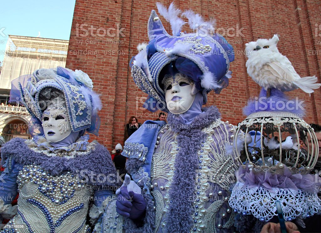 masked persons in magnificent lilac costume during the Carnival stock photo