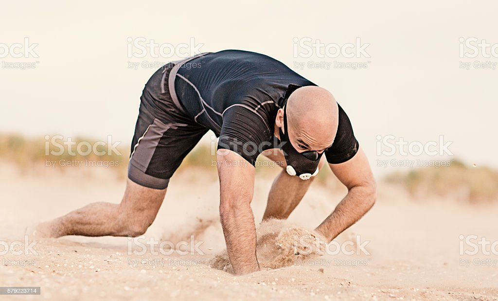 Masked shaved athletic male working out on sandy beach stock photo