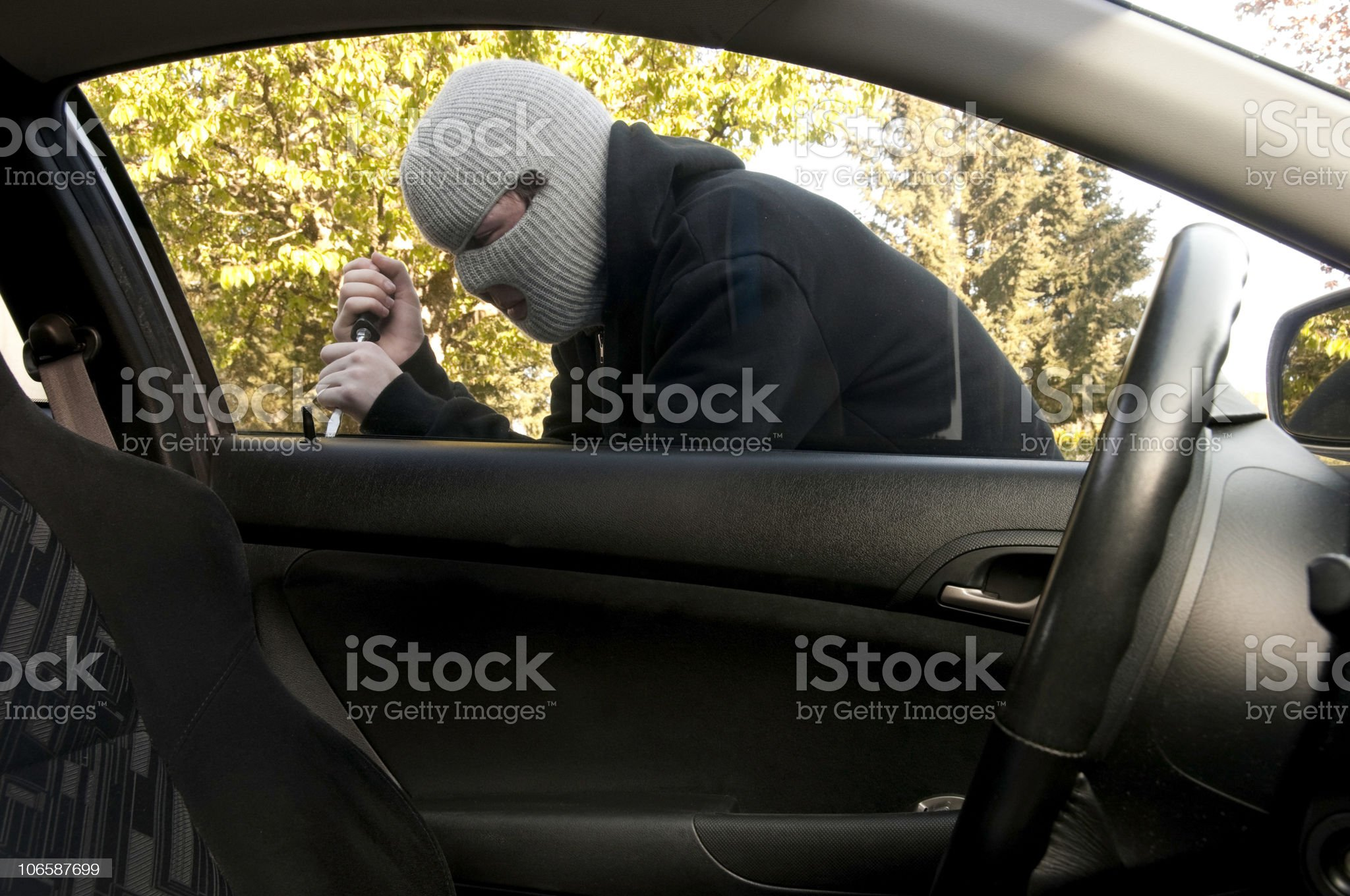 Masked Teenager Breaking into a Car royalty-free stock photo