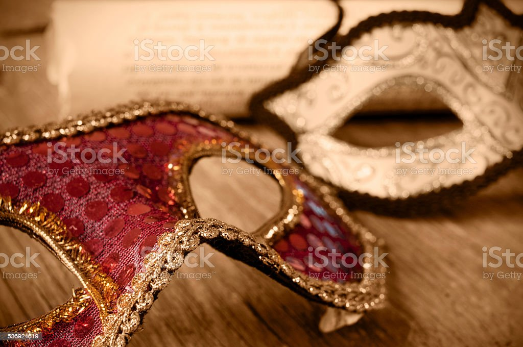 masks and roll on a wooden surface in sepia toning stock photo