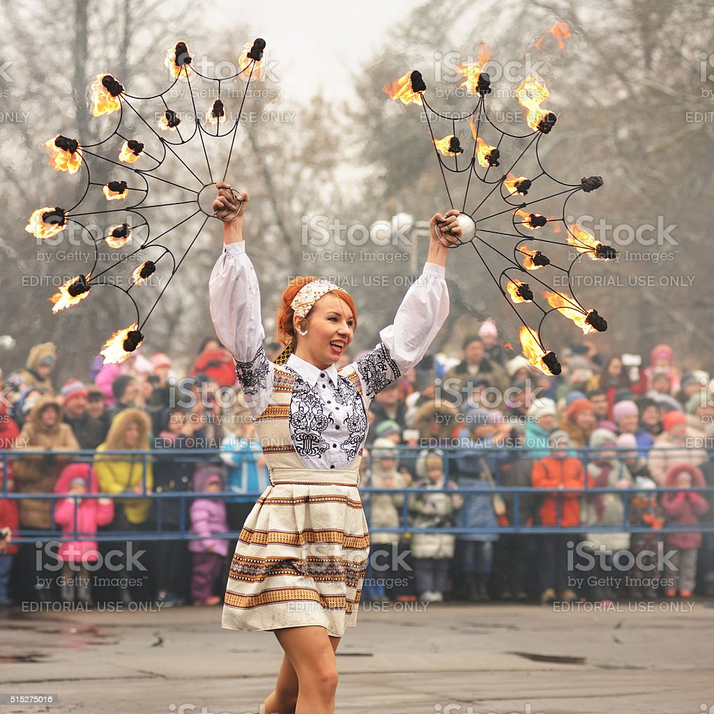 Maslenitsa, Pancake festival. Fire dancer girl in Russian clothes stock photo