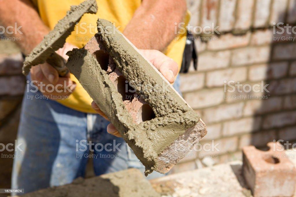 Mason Buttering a Brick with Mortar stock photo