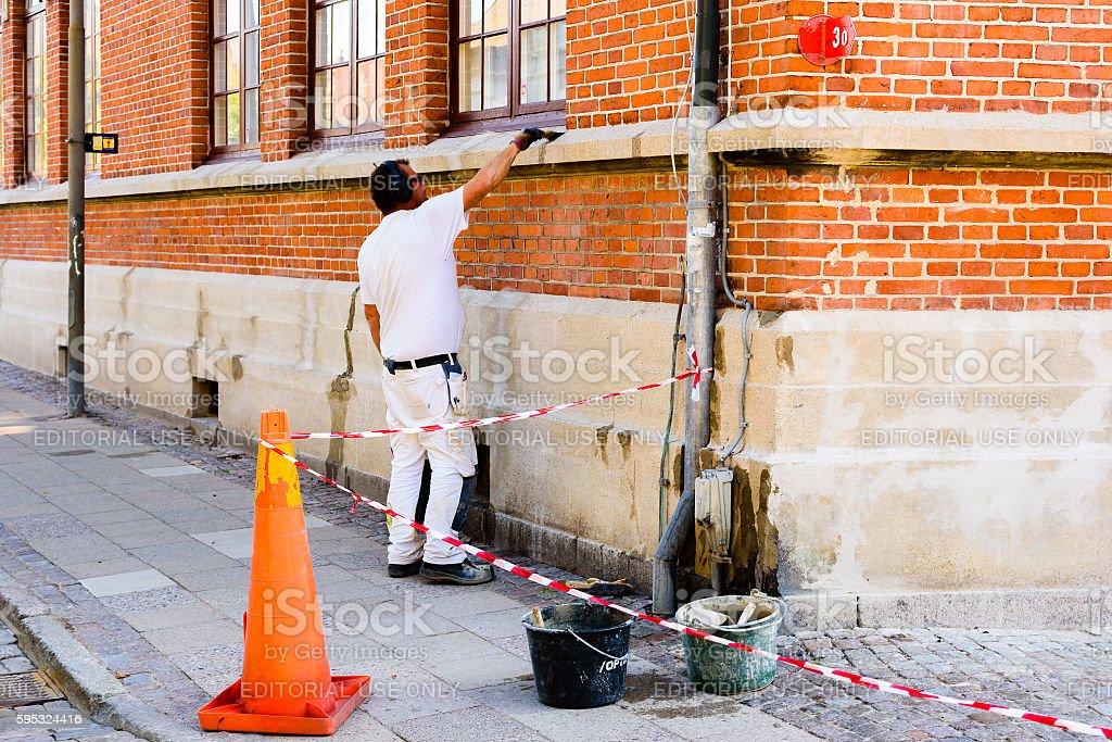 Mason doing repairs in corner stock photo
