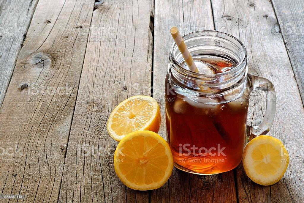 Mason jar glass of iced tea on rustic wood stock photo