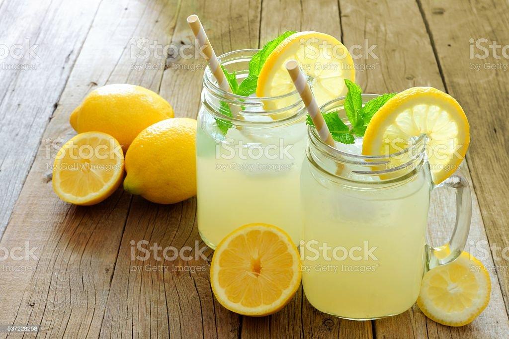 Mason jar glasses of homemade lemonade on rustic wood stock photo