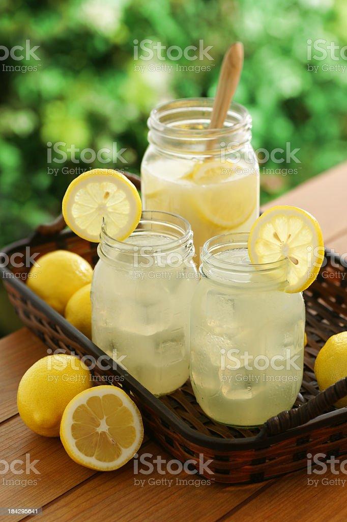 Mason jars filled with fresh lemonade and lemon slices stock photo