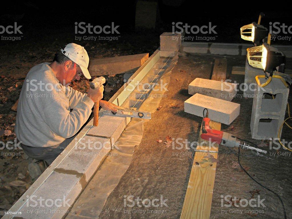 Mason laying block wall at night royalty-free stock photo