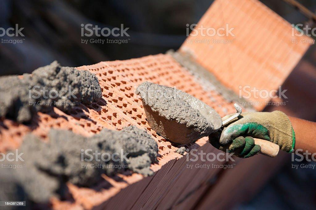 Mason laying bricks at a construction site stock photo