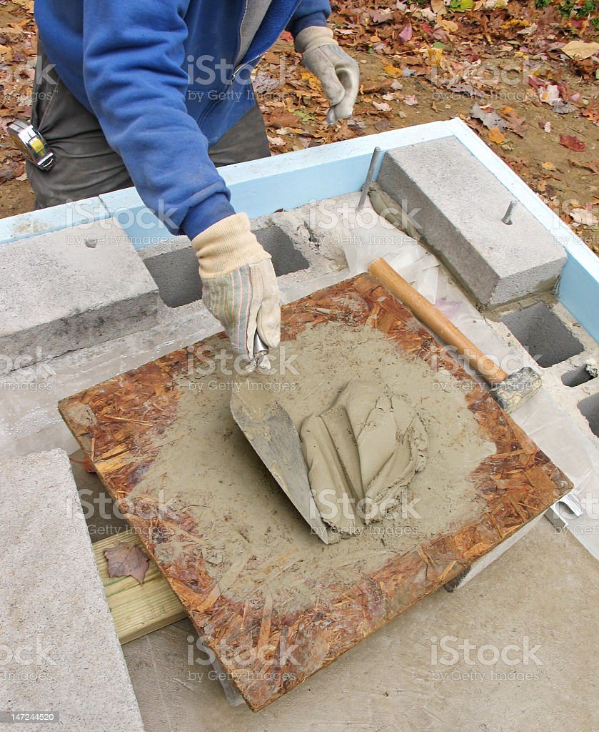 Mason loading trowel with mortar royalty-free stock photo