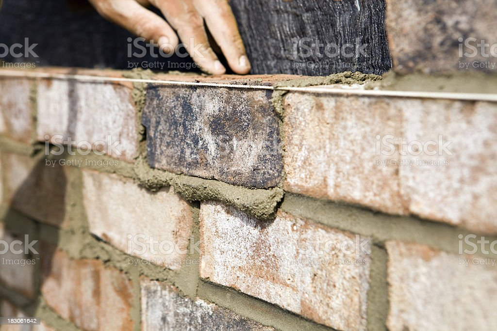 Mason Setting Brick on a new Wall stock photo