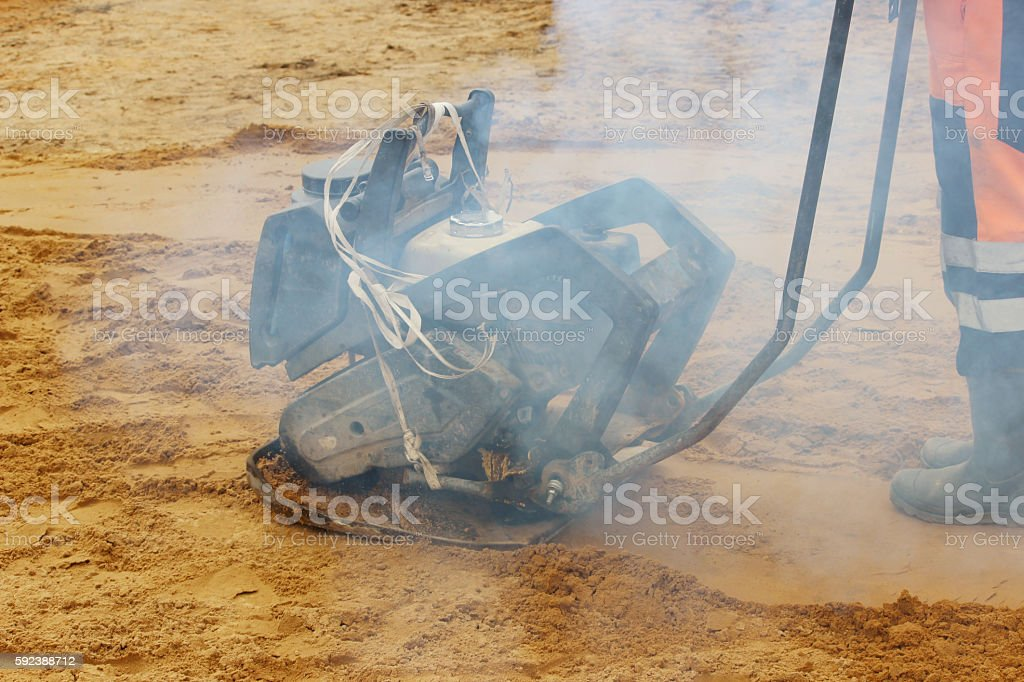 mason tamps the soil using plate compactor before laying paving stock photo