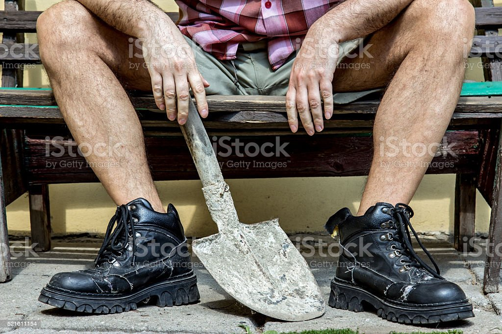 mason with hairy legs in boots resting on a bench stock photo