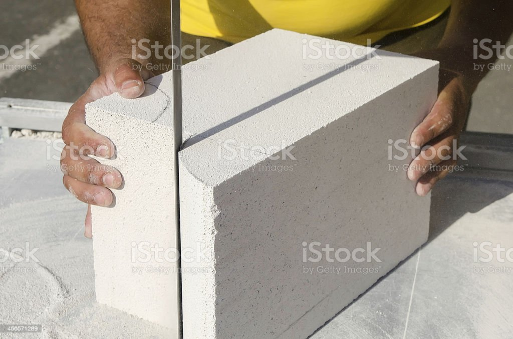 Mason working with construction blocks made from aerated concrete stock photo