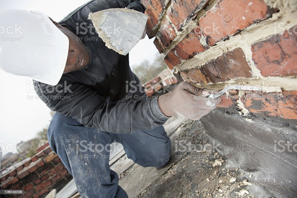 Masons smooths mortar joint in chimney. stock photo