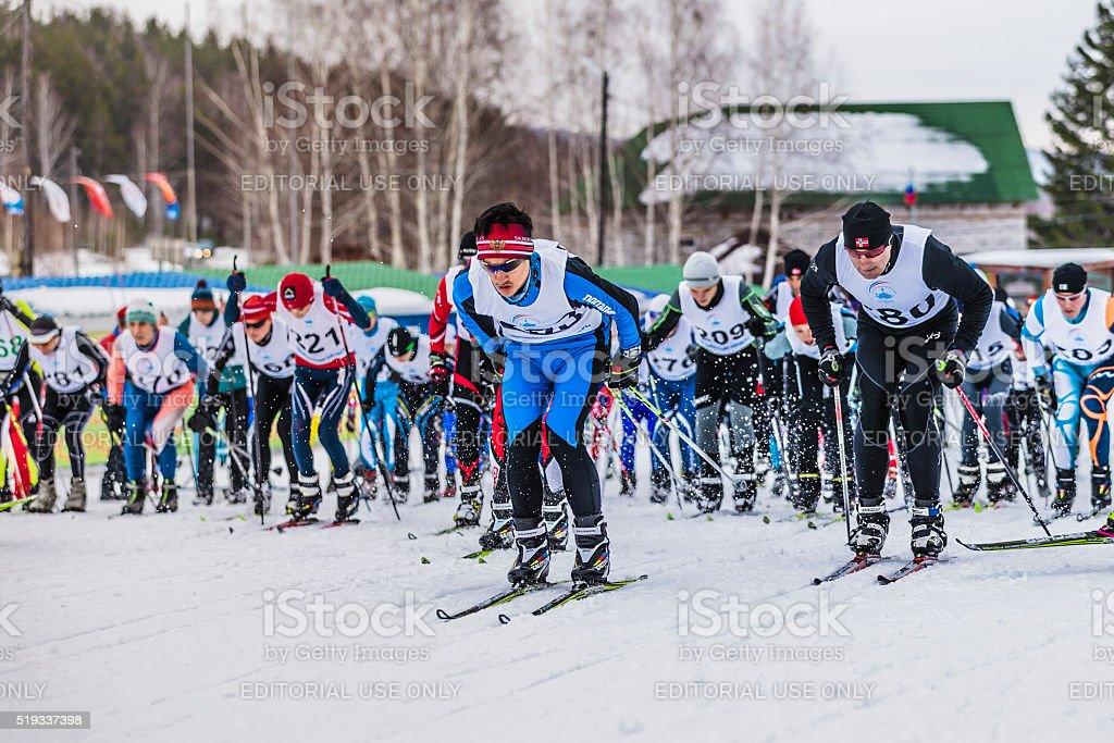 Mass start of skiers athletes marathon distance stock photo